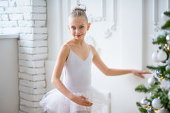 Young ballet dancers learning the lesson near Christm. Young ballet dancers learning the lesson near the wall. Try some new pose Royalty Free Stock Photography