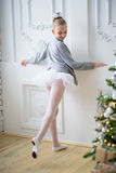 Young ballet dancers learning the lesson near Christm. Young ballet dancers learning the lesson near the wall. Try some new pose Royalty Free Stock Image