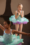 Young Ballet Student Watches Friend. Two little girls in ballet dresses practice in a studio Royalty Free Stock Image