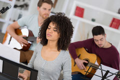 Young band music playing song in recording studio. Young band music playing a song in a recording studio stock image