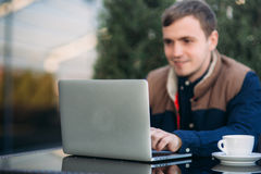 The young bank employee works on a laptop at lunchtime. Royalty Free Stock Photography