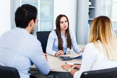 Young bankers analysing financial report. While sitting at office Royalty Free Stock Photography