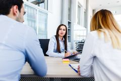 Young bankers analysing financial report. While sitting at office Royalty Free Stock Image