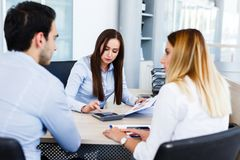 Young bankers analysing financial report. While sitting at office Stock Photography