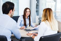 Young bankers analysing financial report. While sitting at office Stock Photo