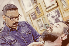 Young barber on a beard shaving session Royalty Free Stock Photo