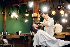 Bearded client sitting in chair for shaving by barber hands with sharp blade. Using traditional tools for male face care. Young barber concentrated in shaving royalty free stock photography