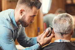 Young barber designing haircut of the aging client in barbershop. Best service ever. Involved skilled professional barber standing in the salon and cutting hair royalty free stock image