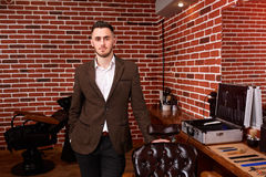 Young barber expert looking at camera and keeping hand on chair while standing at barbershop against brick wall. Portrait of hairdresser in the brown jacket stock photo