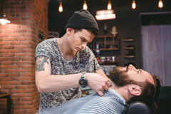 Young barber shaving beard of his client with hair clipper. Young barber with tatoo shaving beard of his client with hair clipper in hair salon stock photo