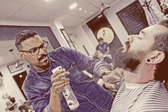 Young barber spraying beard Royalty Free Stock Photography