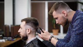 Young barber standing and making stylish haircut of attractive man with clipper in barbershop. Bearded man is sitting on stock footage