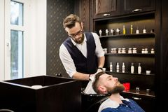 Young barber wiping customer hair with towel. Portrait of young barber wiping customer hair with towel Royalty Free Stock Images