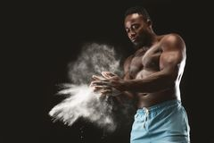 Young bare-chested african american sportsman applying talcum powder. Black studio background, empty space stock photos