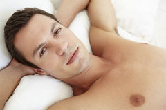 Young Bare Chested Man Relaxing On Bed Stock Image