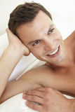 Young Bare Chested Man Relaxing On Bed Stock Images