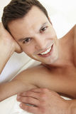 Young Bare Chested Man Relaxing On Bed Royalty Free Stock Images