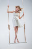 Young bare-footed girl on swing looking down. Stock Photo