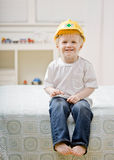 Young barefoot boy sitting on bed in bedroom Royalty Free Stock Photo