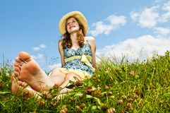 Young barefoot girl sitting in meadow Stock Image