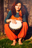 Young barefoot lady drummer playing on her djembe drum on rustic wooden door background Stock Image