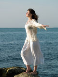 Young barefoot Lady on Stone arms outstretched. Young beautiful barefoot woman staying on sea stone arms outstretched Stock Image