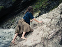 Young barefoot woman climbing rocks Stock Photography
