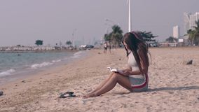 Young barefoot woman in gray summer dress reads book. Sitting on ocean sandy beach near black sandals stock video footage