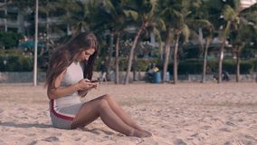 Young barefoot woman in gray texts on phone sitting on sand. Young barefoot woman in gray summer dress sits on beach sand and types on smartphone against green stock video