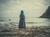 Young barefoot woman with headscarf on beach. A young barefoot woman wearing a headscarf is standing on a beach on a cold and windy day royalty free stock photos