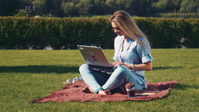 Young barefoot woman using a laptop outdoors. Young attractive blond barefoot woman using a laptop outdoors sitting on a rug on the grass in a garden in the stock video