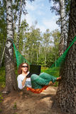 Young barefooted woman in dark sunglasses lies in hammock. At birchwood and works on notebook stock image