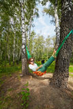 Young barefooted woman in dark sunglasses lies in hammock. Outdoors with notebook royalty free stock photos