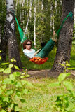 Young barefooted woman in dark sunglasses lies in hammock. Outdoors and works on notebook stock photo