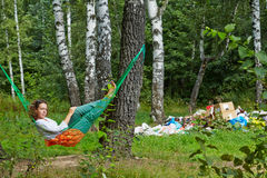 Young barefooted woman with discontented face lies in hammock. At birchwood near pile of garbage stock photos