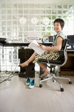 Young barefooted woman sitting in office, holding paperwork, smiling, portrait Stock Image