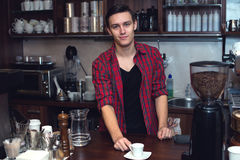 Young barista  at cofeeshop cafe made a cup of Royalty Free Stock Photo