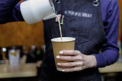 Young barista girl pouring a cappuccino glass stock photo