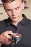 Young barista holding bung with coffee. Royalty Free Stock Photo