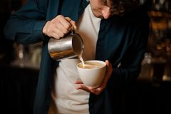 Young barista pouring some milk into a coffee cup. Making latte art in a coffee shop Royalty Free Stock Image