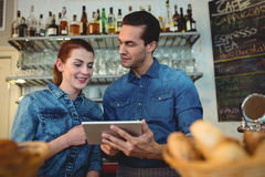 Young baristas with digital tablet at cafe. Young male and female baristas with digital tablet at cafe Royalty Free Stock Photo