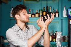 Young barman in bar shaking and mixing alcohol cocktail. Young barman in bar interior shaking and mixing alcohol cocktail. Professional bartender at work with royalty free stock photography