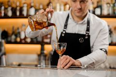 Young barman adding alcoholic drink into an elegant glass Royalty Free Stock Photography