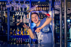Young barman juggles bottles. Flaring. Royalty Free Stock Photography