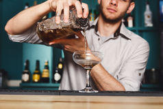 Young Barman mixing cosmopolitan cocktail Royalty Free Stock Photo