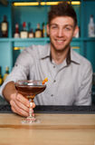 Young Barman offers alcohol cocktail in night club bar Royalty Free Stock Images