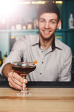 Young Barman offers alcohol cocktail in night club bar Royalty Free Stock Photo
