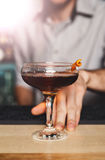 Young Barman offers alcohol cocktail in night club bar Stock Photography