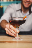 Young Barman offers alcohol cocktail in night club bar Stock Photos