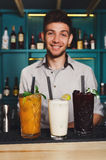 Young Barman offers alcohol cocktails in night club bar Stock Image